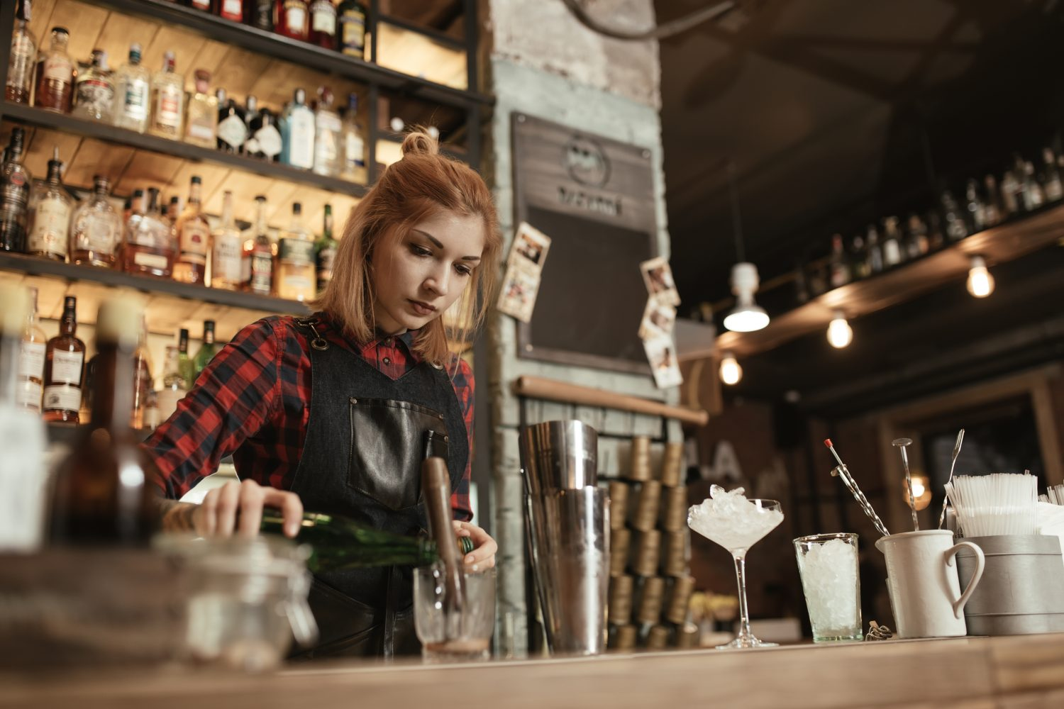 Woman bartender making an alcohol cocktail at the bar